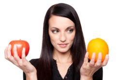 Dame mit je einer Orange und einem Apfel in der Hand, um zu vergleichen